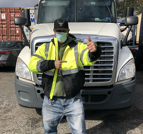 Man wearing a neon yellow jacket and a face mask, giving us a thumbs up and a rock n roll sign with his hands, standing in front of a white semi-truck, in a container yard