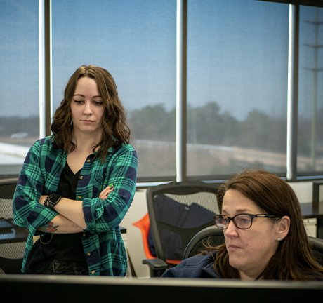two women, one wearing a green flannel standing behind the other woman who is sitting behind a computer monitor, in an office