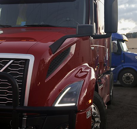 close up image of a red truck with a blue truck in the background