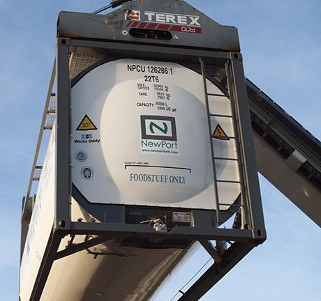 white ISO bulk container being lifted in the air by a crane