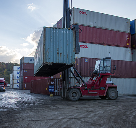 image of a container fork-lift, lifting a a container in a container yard