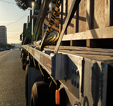 image of the side of a flatbed truck on a street with a sunset in the background