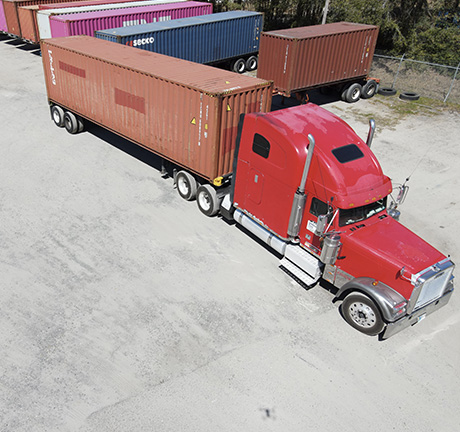a red shipping truck with a brown container, parked in front of multiple containers.