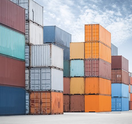 Shipping containers stacked at various heights, with a cloudy sky in the background
