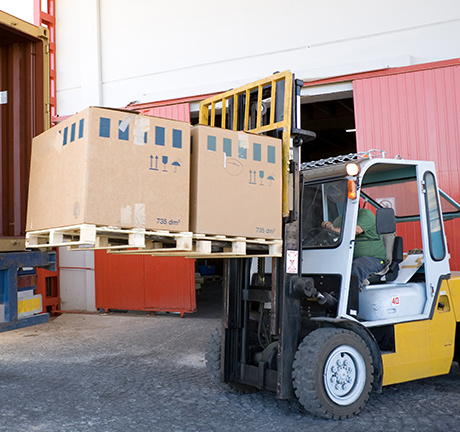 fork-lift loading product into a truck from a warehouse