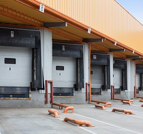 5 white garage doors under an orange roof. This is an image of a docking station.