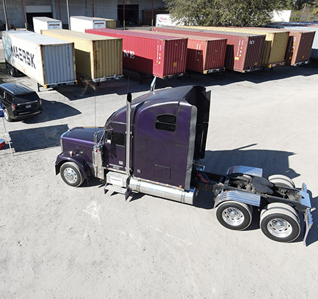 Purple shipping truck in a container yard